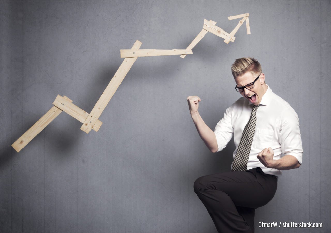 Konzept: Gewinner im Geschäft. Thrillter junger Geschäftsmann jubelt vor einem positiven Geschäftsdiagramm, einzeln auf grauem Hintergrund.