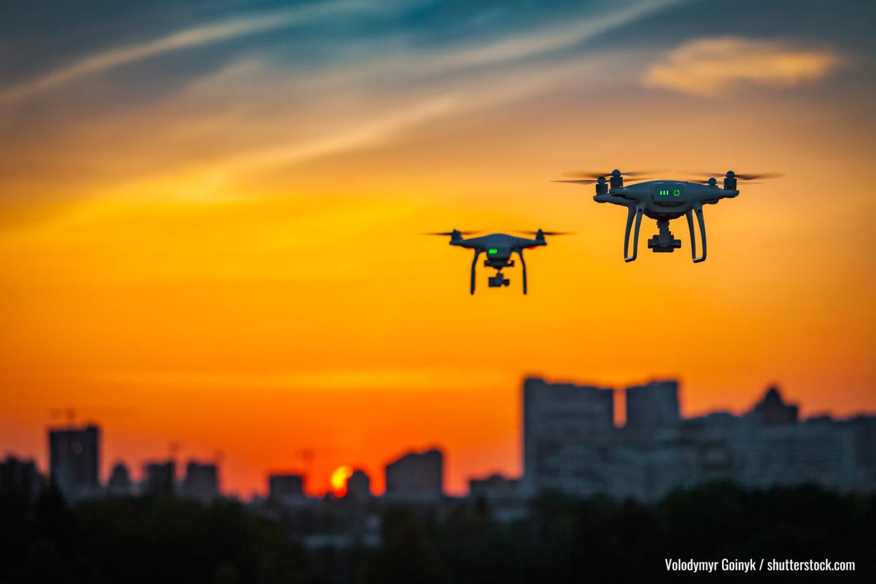 Zwei drone Quad-Koper mit hochauflösender Digitalkamera, die Luftaufnahmen über spektakulärem orangefarbenem Sonnenuntergang fliegen. Stadtlandsilhouette mit Sonne geht in den Hintergrund.Fahrzeug bei Sonnenuntergang und Kopienraum