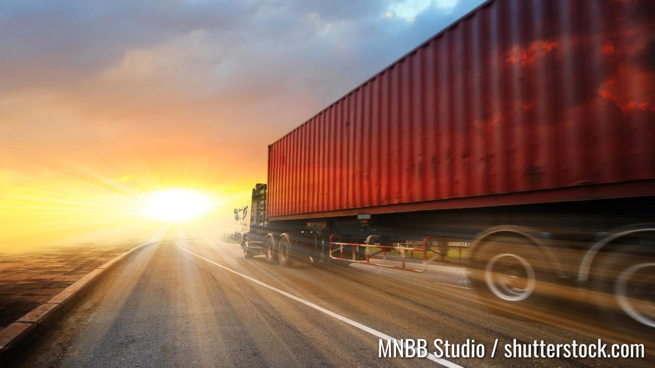 Generische große LKWs, die bei Sonnenuntergang auf der Autobahn fahren - Verkehrskonzept , große LKW-Container