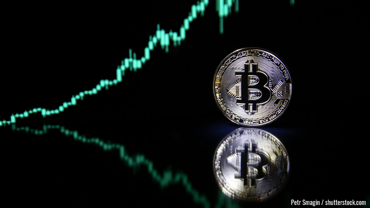 Bitcoin on the background of bullish stock chart on a black background. cryptocurrency coin on black background with reflection. increase in the value of bitcoin